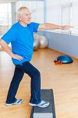 stock photo of step aerobics  - Full Length of confident senior man doing step aerobics in health club - JPG