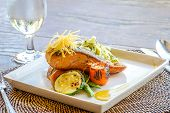 picture of salmon steak  - grilled salmon steak served with pasta and vegetables in a small outdoor restaurant - JPG