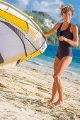 stock photo of kites  - young woman kite surfer getting ready for kiting on sand tropical beach - JPG