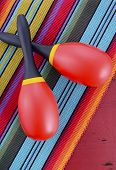 picture of maracas  - Happy Cinco de Mayo background with red and yellow maracas on Mexican style fabric and distressed red wood table - JPG