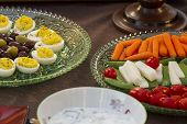 image of kalamata olives  - Deviled eggs kalamata and green olives served with carrots jimaca and cherry tomatoes as a before dinner horderve