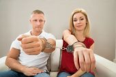 foto of handcuffed  - Portrait Of Unhappy Young Couple Handcuffed Together - JPG