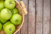 pic of crisps  - Wicker basket of crisp fresh green apples displayed on a wooden picnic table or at a farmers market for fresh produce direct from the farm overhead view with copyspace - JPG