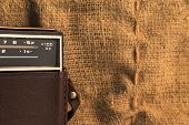 picture of transistor  - Part of an old transistor radio in a leather case on a background of a burlap - JPG