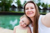 image of selfie  - Happy family mother and her adorable little daughter on summer vacation taking selfie with smartphone - JPG