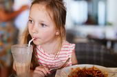picture of lunch  - Portrait of adorable little girl having  lunch at restaurant - JPG
