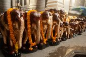 stock photo of brahma  - Carved wooden elephant People bring offerings to Erawan Shrine  - JPG