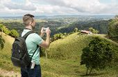 image of memento  - Tourist man taking photo of hills in Dominicana - JPG
