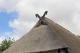 picture of soffit  - The thatched roof of the Low German hall houses is bordered traditionally with wooden soffits in form of a horse head - JPG