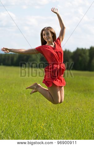 Young Girl In A Red Dress Jumping In A Field Coniferous Forest