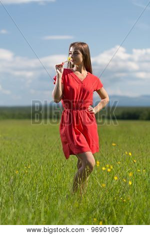 20 Year-old Girl In Red Dress Sniffing A Yellow Flower