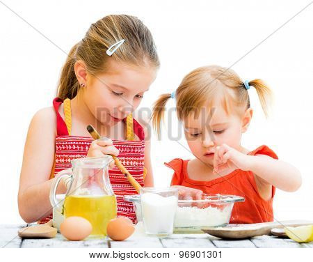 two cute little sisters cooking, on a white background