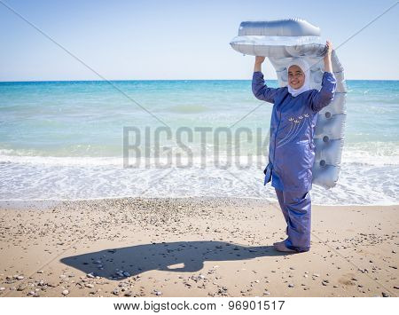 Happy Muslim girl, on summer vacation with swimming suit