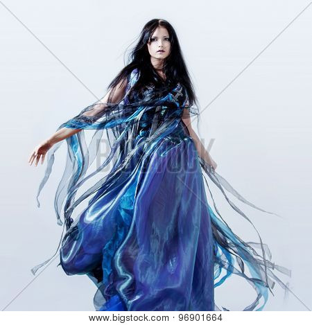 Fashion photo of young magnificent woman in blue dress. Studio portrait