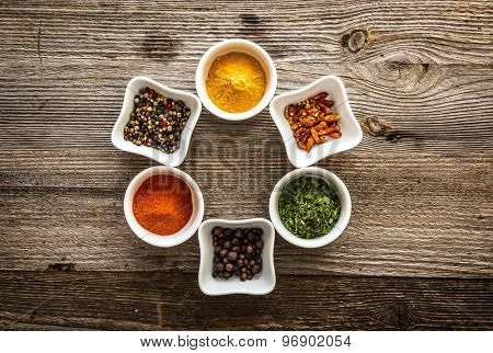 aromatic colorful spices in bowls on wooden background