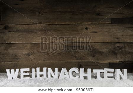 The word christmas in white german letters on wooden old rustic background.