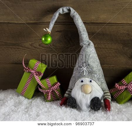 Gnom santa with green and red christmas presents in rustic country style.