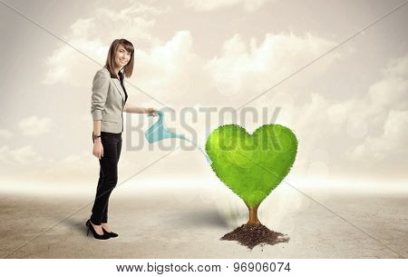 Business woman watering heart shaped green tree concept on background