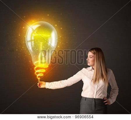 Businesswoman holding a shining, idea bulb