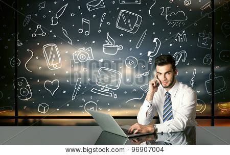 Businessman sitting at table with hand drawn social media icons and symbols
