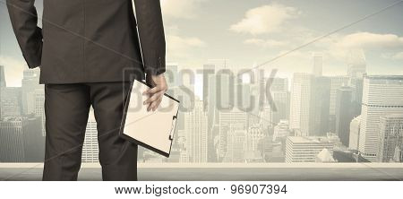 Businessman from the back in front of a city view on the window
