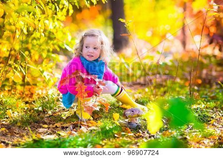 Little Girl Picking Mushrooms In Autumn Forest