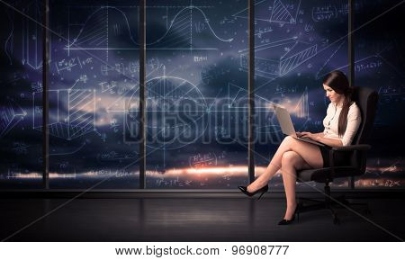Businesswoman holding laptop in office room with graph charts on window concept
