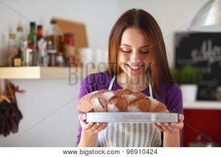 Young woman holding tasty fresh bread in her kitchen