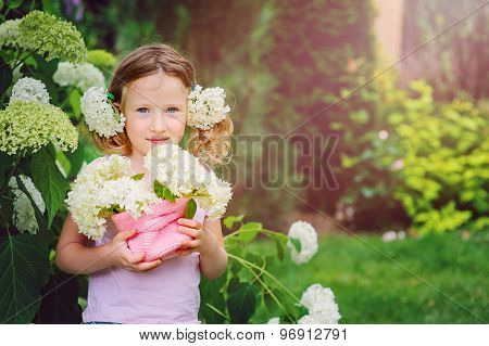 cute happy child girl playing with hydrangea bouquet in summer garden