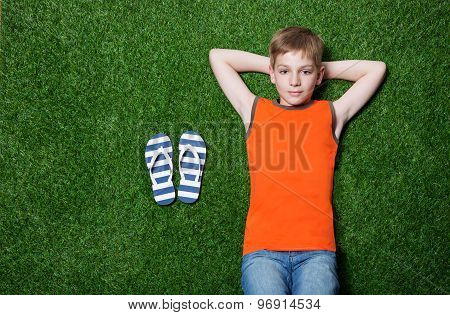 Boy lying on green grass with slippers