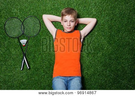 Boy lying with badminton racket on green grass