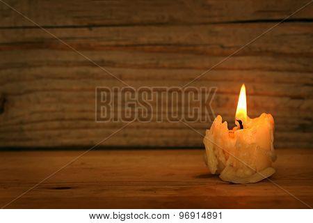 Burning old candle on wooden vintage background.