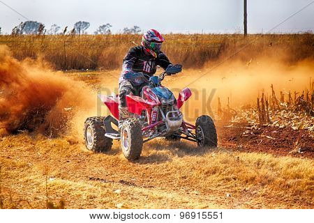 Hd- Quad Bike Kicking Up Trail Of Dust On Sand Track During Rally Race.
