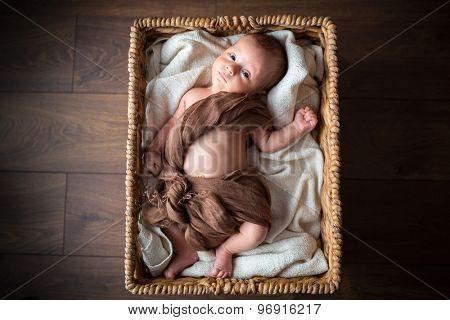 Newborn baby boy lying down inside the wicker basket