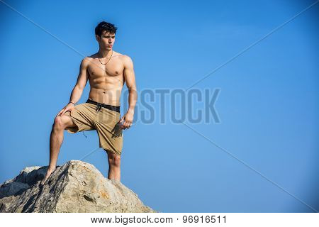 Young shirtless athletic man climbing on rock by water on ocean shore