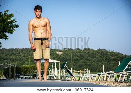 Young shirtless athletic man standing at the beach