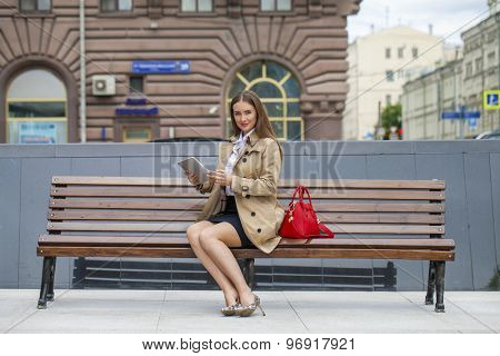 Business woman in a beige raincoat holding a tablet in the summer city