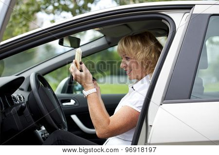 An elderly woman gets himself makeup sitting in car