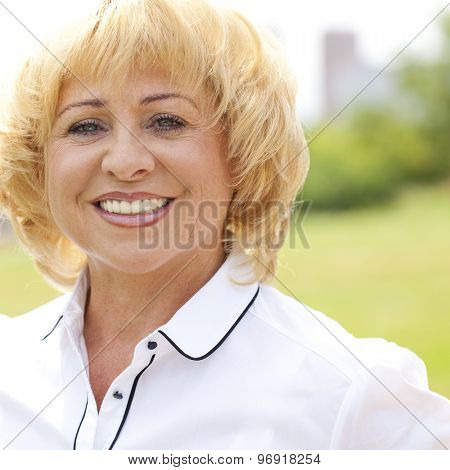 Happy elderly woman in a white jacket on the background of summer park