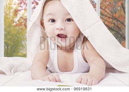 Cheerful Male Infant Under A Towel