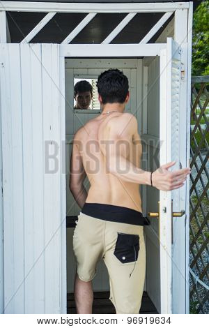 Young Man Standing in Doorway of Rustic Beach Hut