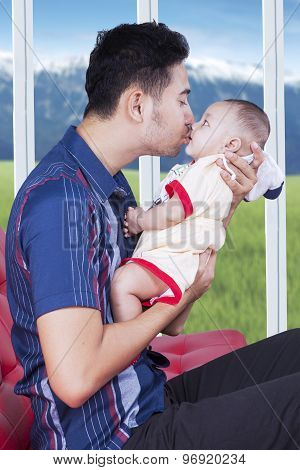 Father Sitting On Couch While Kissing His Son