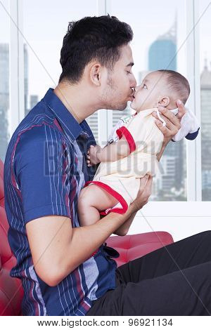 Loving Father Kissing Baby In Apartment