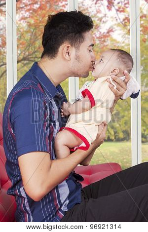Man Sitting On Sofa While Kissing His Baby
