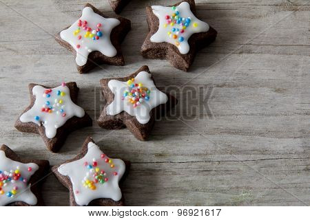 Star Cookies with Icing and Sprinkles on Wood