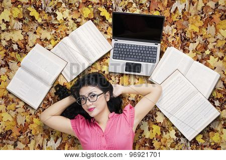 Pretty Student Relaxing On Autumn Leaves