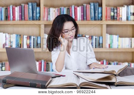 Student Sitting In Library While Reading Book