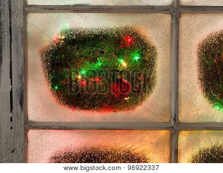 Snowy Windows With Red Ornament Hanging On Fir Tree With Glowing Lights During Night Time