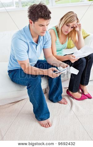 Stressed Young Couple Calculating Bills Sitting In The Living-room