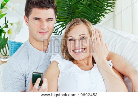 Blissful Woman Showing Her Wedding Ring To The Camera Lying With Her Boyfriend